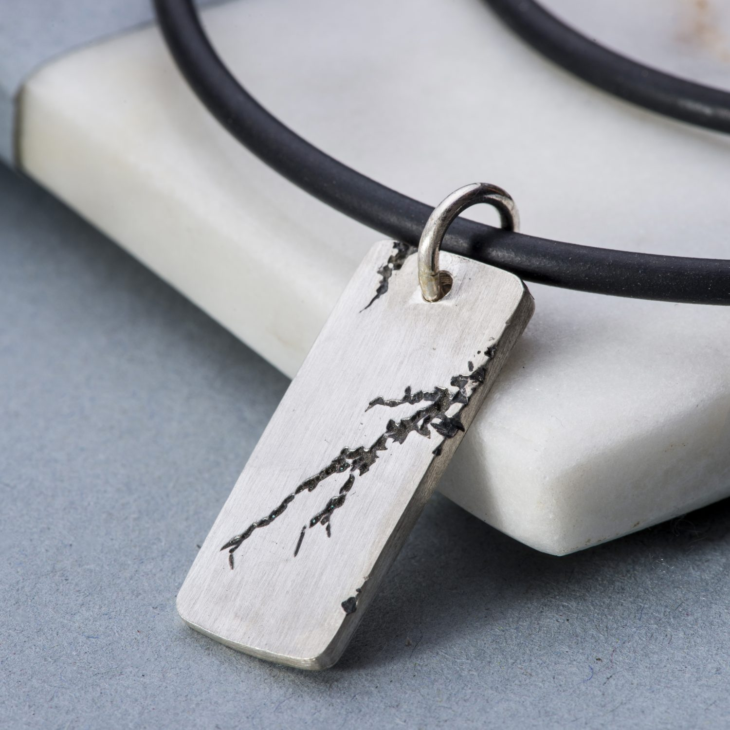 Men's silver pendant on rubber with rip detail and personalsiation