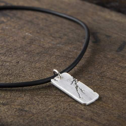 A distinctive chunky silver men's pendant hangs off a black rubber cord. The silver dog tag is solid matt silver with contrasting black crack.